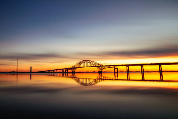 Long silhouetted bridge with an arch crossing a crystal clear calm body of water at sunset.