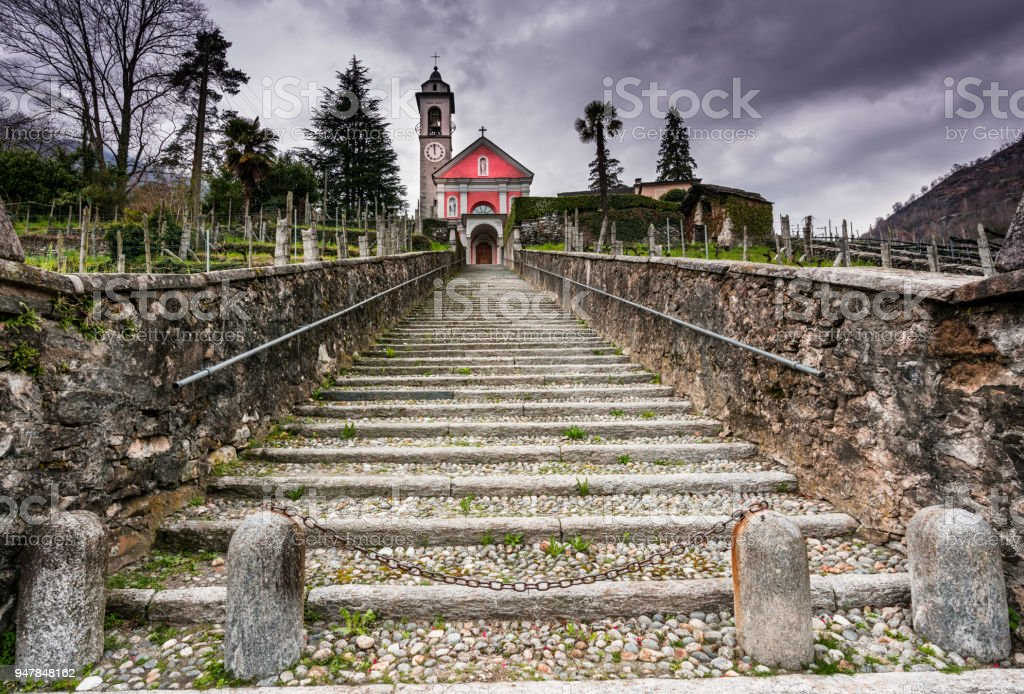 long stairs leading up to an old rose colored church under an expressive overcat sky stock photo