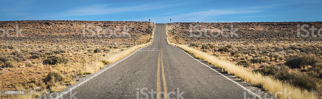 Long straight desert road through dry landscape Monument Valley Utah stock photo
