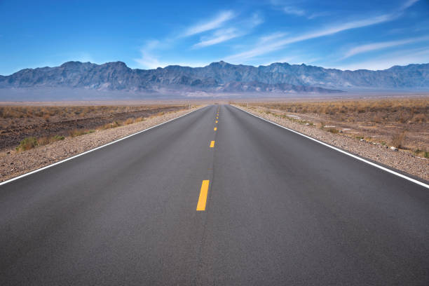 A Long Straight Empty Road An empty desert road in Death Valley National Park, California, United States of America. middle of the road stock pictures, royalty-free photos & images