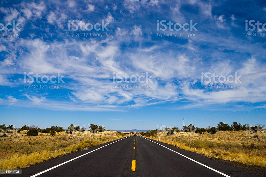 Long straight road under wispy clouds Long straight road under wispy clouds. Shot in Arizona on Route 64 facing north toward the Grand Canyon. Absence Stock Photo