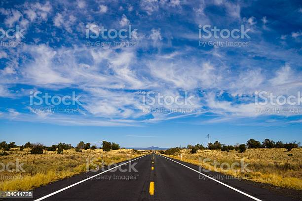 Long Straight Road Under Wispy Clouds Stock Photo - Download Image Now