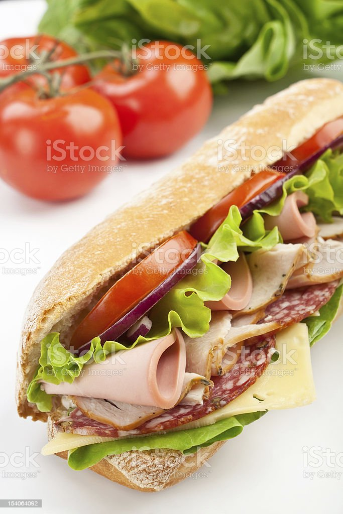 long subway baguette sandwich with meat, vegetables and cheese stock photo