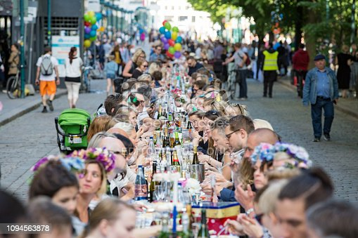Helsinki, FINLAND - JUNE 12, 2018: Long table with lots of people eating and drinking together. The Day of City Celebration in centre of Helsinki. Finnish your dinner under the sky.
