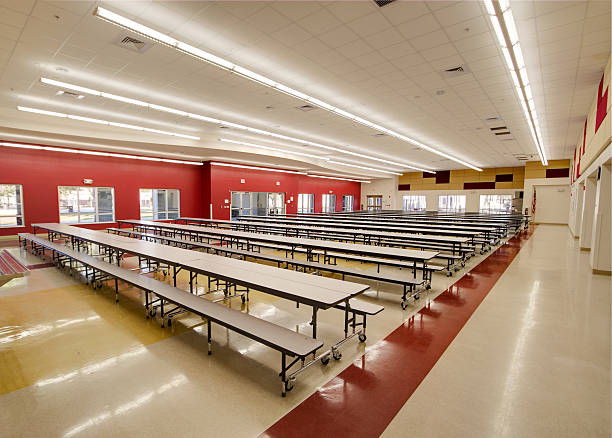 Long tables in an empty red and beige high school cafeteria stock photo