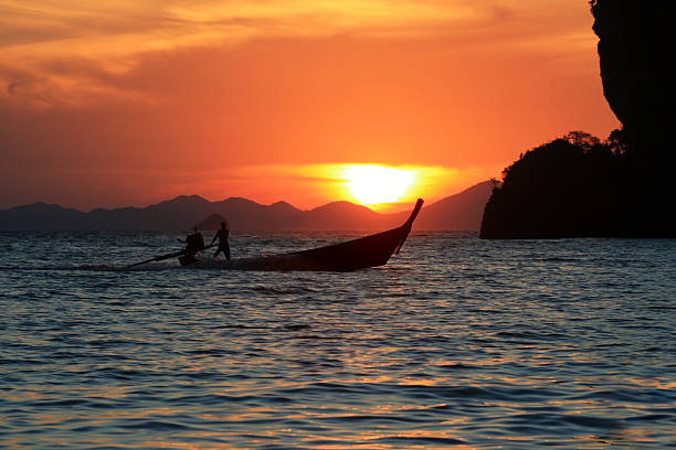 long tail boat at sunset stock photo