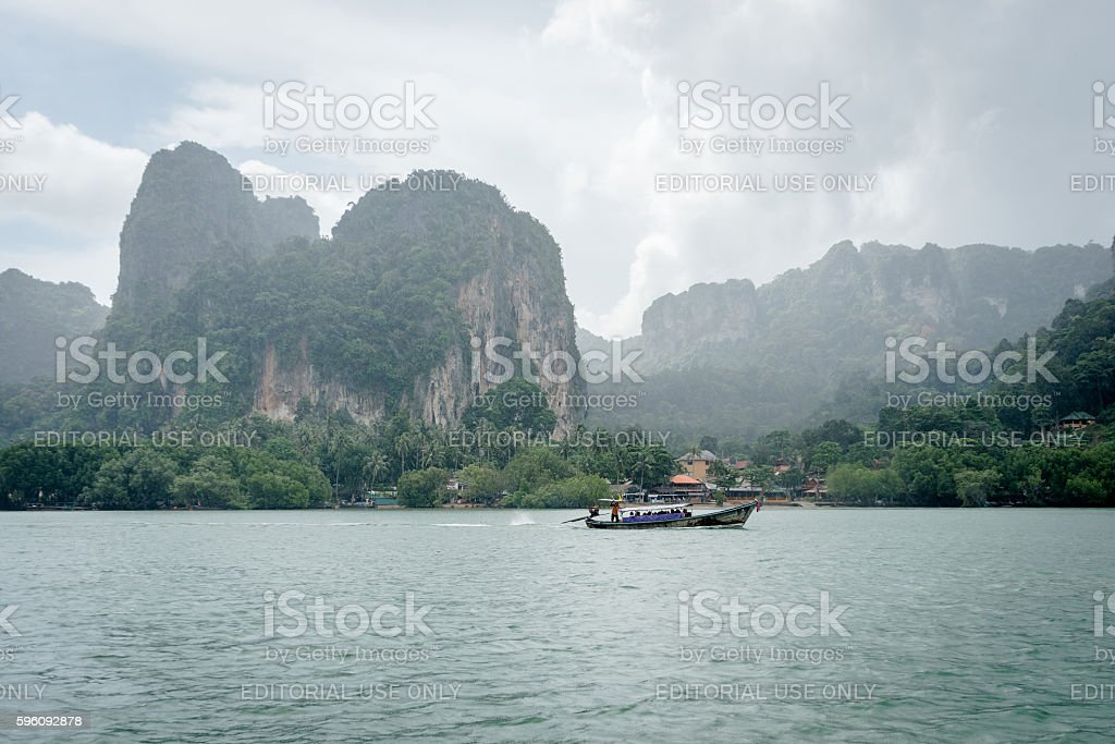 Long tail boat in sea under high mountain and clouds royalty-free stock photo