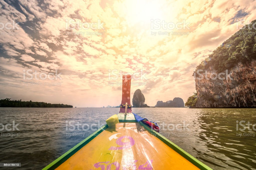 A long tail boat is sailing in the Ao Phang Nga (Phang Nga Bay) National Park at sunset. Phang Nga is one of the southern provinces (changwat) of Thailand. stock photo