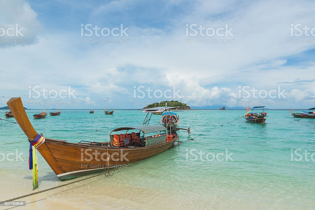 Long tail boats lined with blue sky at Koh Lipe. stock photo
