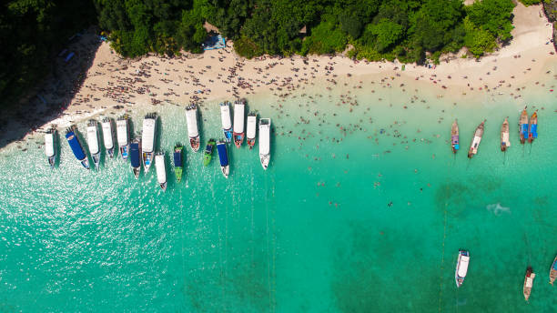 maya bay, koh phi phi leh, thailand - may 16, 2018. long tail boats mooring in the famous maya bay with tourists on the beach - phuket stock photos and pictures