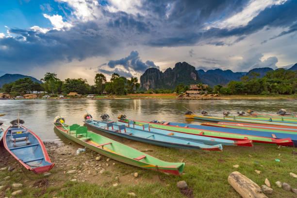 longtailboote am sonnenuntergang am song fluss, vang vieng, laos. - vang vieng stock-fotos und bilder
