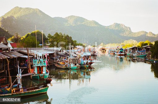 Long tail fishing boats on the pier in the village in Thailand