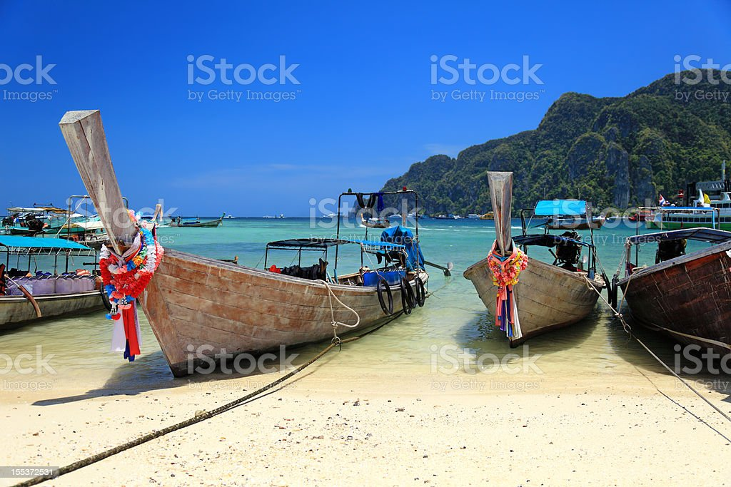 Long tail wooden boats stranded at the beach royalty-free stock photo