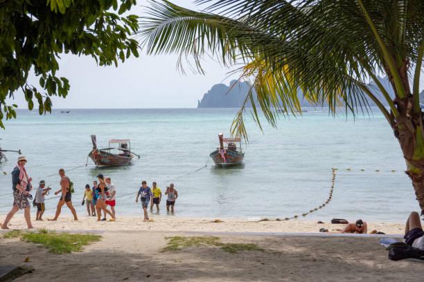 Caudas longas e turistas na Ilha Phi Phi, Tailândia. - foto de acervo