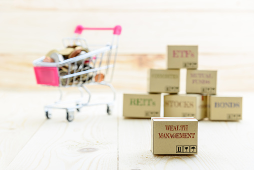1155852718 istock photo Long term sustainable and wealth management with risk diversification concept : Box printed with financial instrument / investment products i.e stocks, ETFs, bonds, REITs and coins in a shopping cart. 1036559144