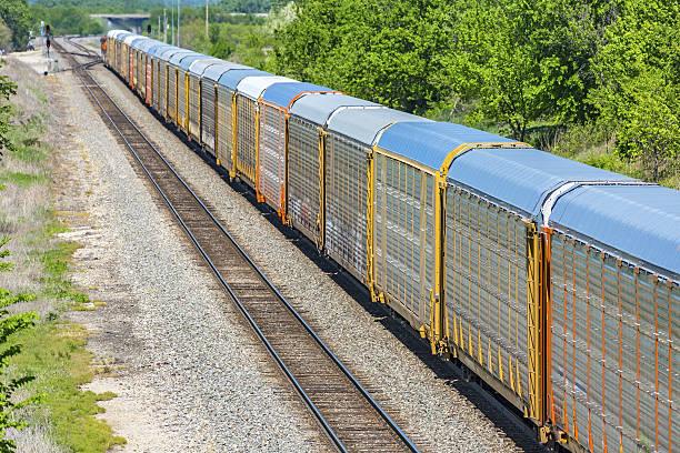 long train transporting new motor vehicles in covered autoracks - aufgemotzte trucks stock-fotos und bilder