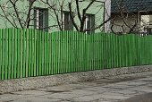 istock long wall of a private fence of green wooden boards 1215471845