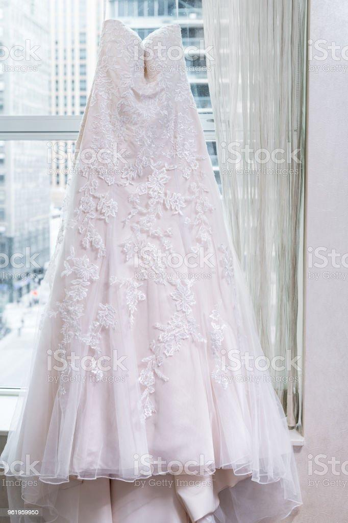 fotografía de vestido de novia largo colgar en percha de ventana con