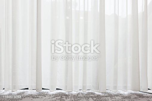 Long, white, semy see-through curtains hanging in the window