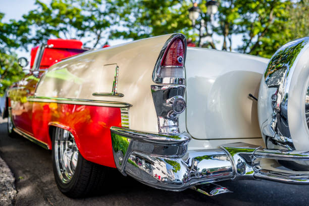 Long white vintage retro convertible car with red trim and chrome moldings exhibited at a provincial town street exhibition stock photo