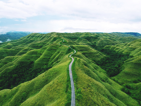 Aerial drone view: A long winding road between hills of green grass in remote parts of the Indonesian island of Sumba