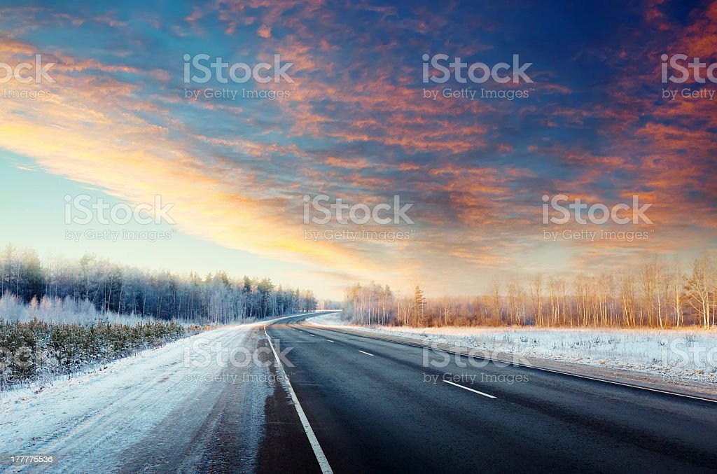 A long winter road with a pale red sky stock photo