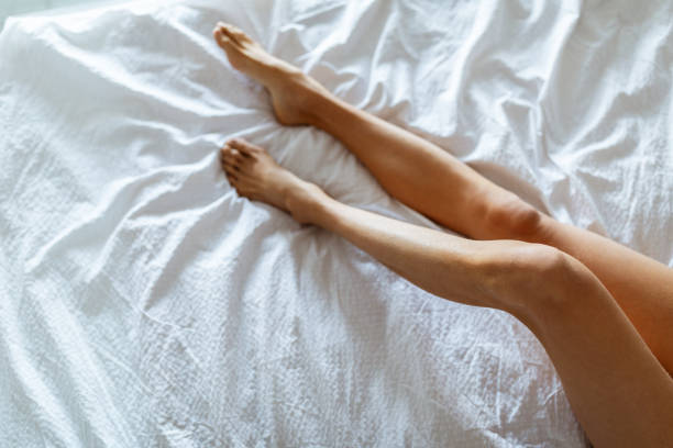 Long Woman Legs With Smooth Soft Skin On White Bed stock photo