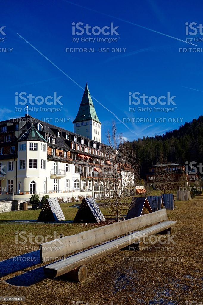 Long wooden bench and a hotel in the background stock photo