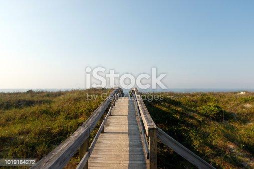 Long wooden boardwalk through the green dune grass to the Atlantic Ocean, Sunset Beach, North Carolina