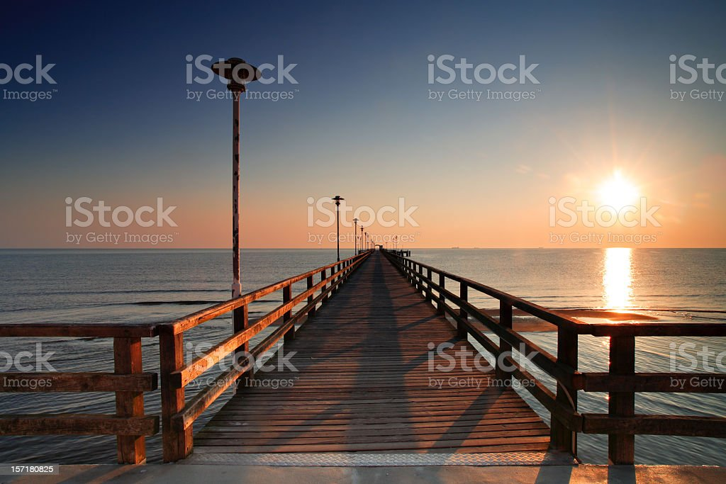 Long Wooden Dock and Ocean at Sunrise royalty-free stock photo