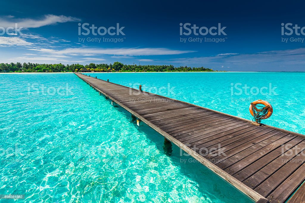 Long wooden jetty over atoll and tropical island in Maldives stock photo