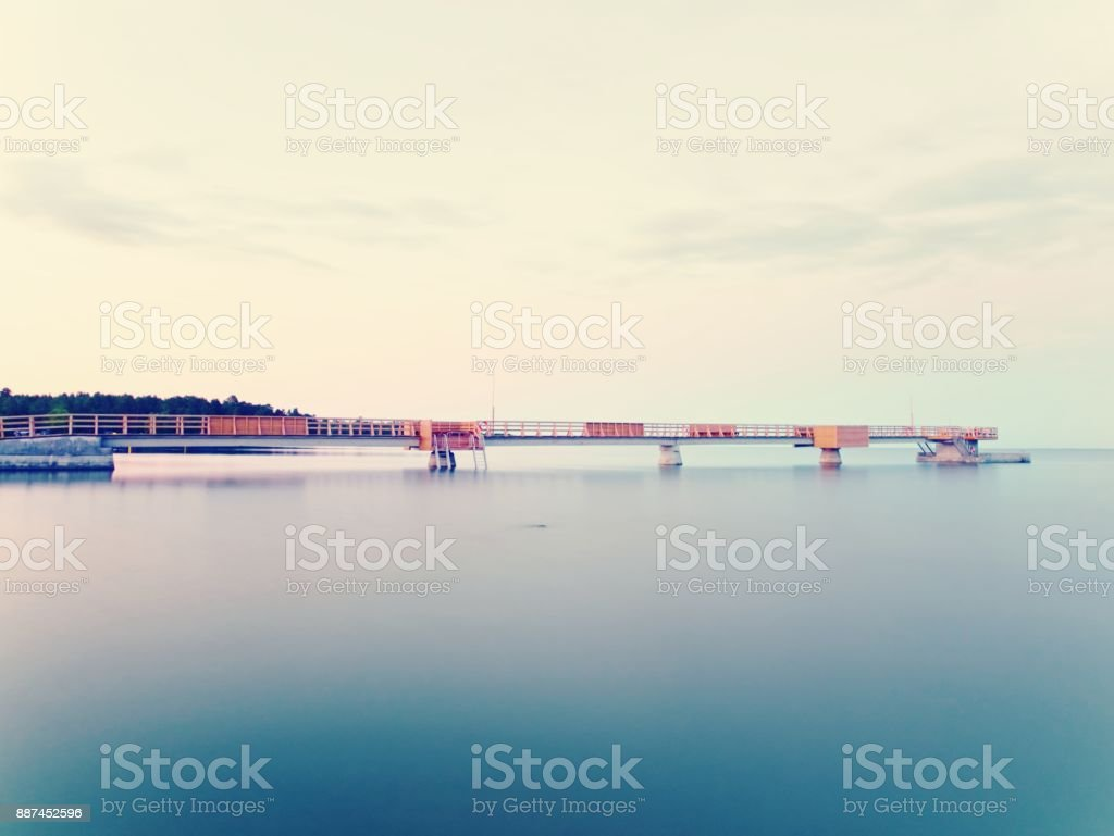 Long wooden pier on the Baltic coast during morning. Cold weather,...