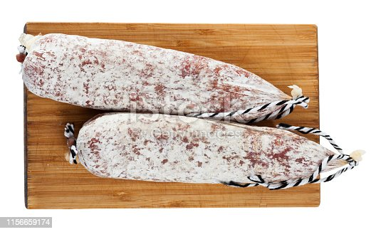 Catalan sort of popular Spanish Longaniza sausage from minced pork on wooden board. Isolated over white background