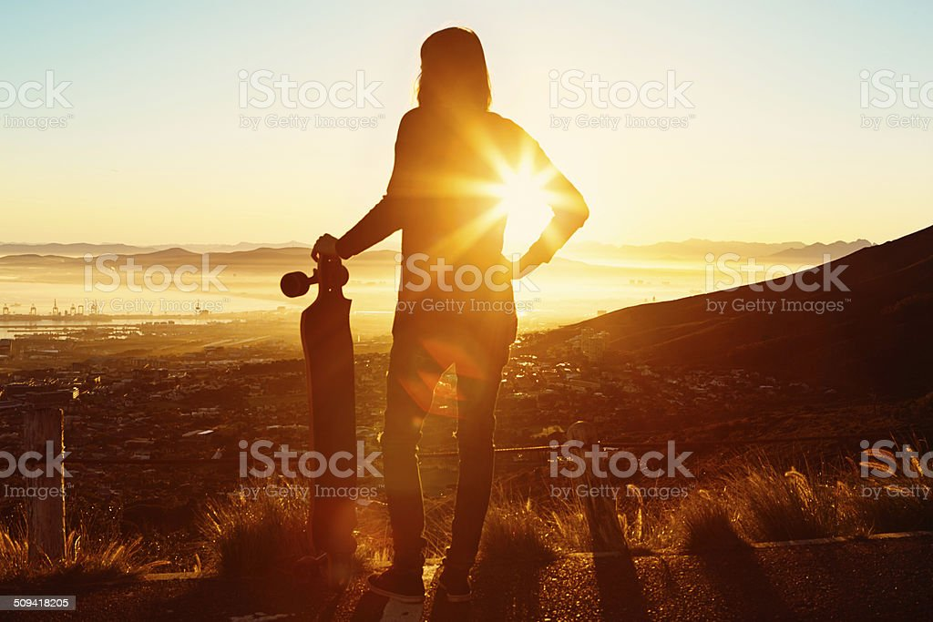 Longboarder silhouetted by rising sun on Table Mountain contour path stock photo