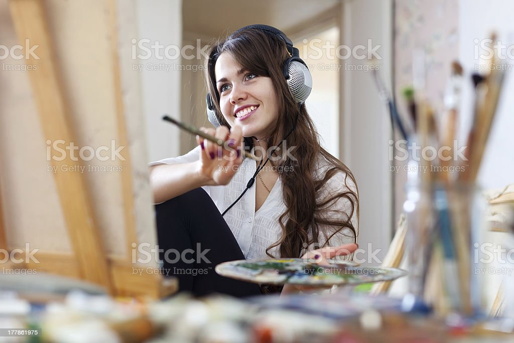 Long-haired  artist  in headphones paints picture stock photo