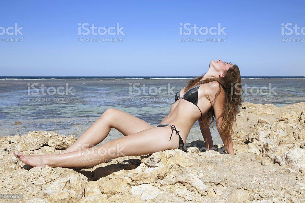 Long-haired girl sunbathing on stones royalty-free stock photo