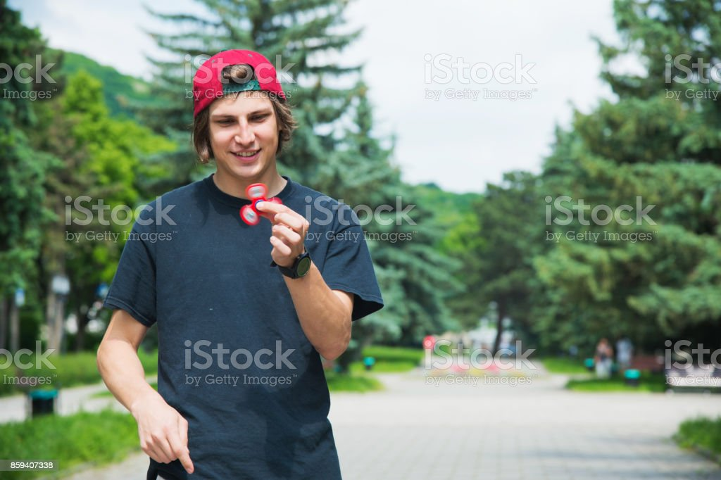 A long-haired hipster in a cap sits on a bench and spins a fidget-spinner stock photo