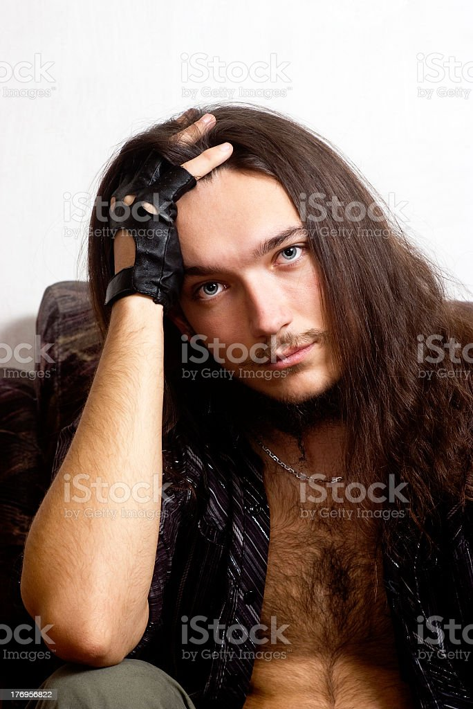 Long-haired man grafted hand behind his head. royalty-free stock photo