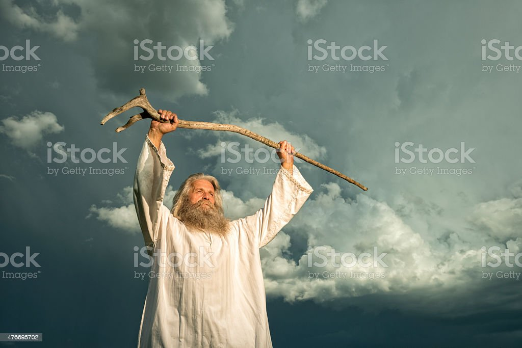 long-haired prophet gesturing in front of dramatic sky stock photo