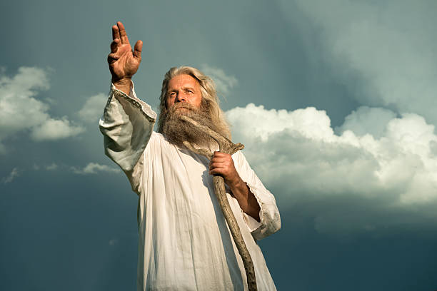 long-haired prophet gesturing in front of dramatic sky - god stock photos and pictures