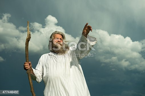 An old man with long grey hair and a long grey beard standing in front of a dramatic dark sky. He is wearing a white toga and holding a wooden bar. His arm is stretched out for giving a sign or pointing at something and he is looking up to the sky.