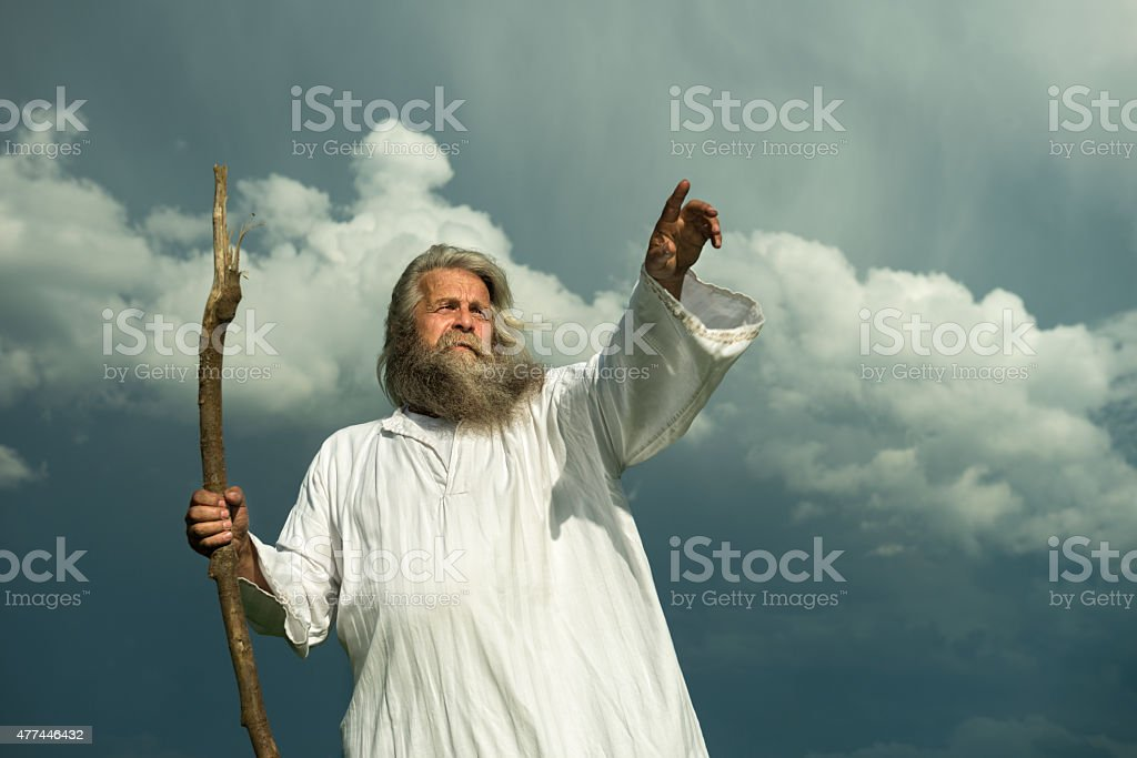 long-haired prophet pointing in front of dramatic sky stock photo