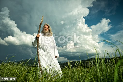 An old man with long grey hair and a long grey beard standing in the grass in front of a dramatic dark sky. He is wearing a white toga and holding a wooden bar.