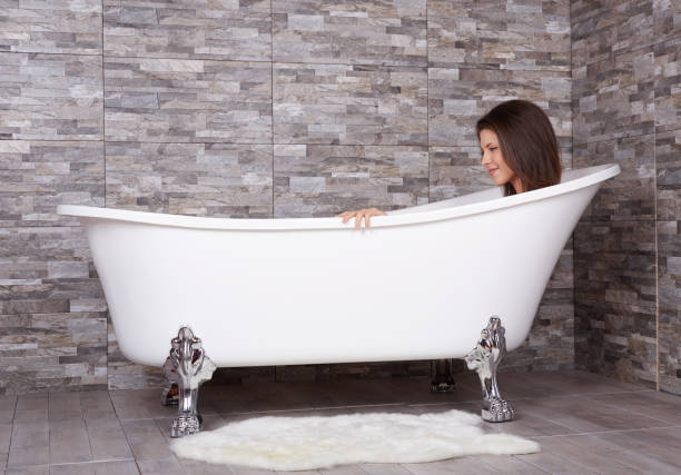 Long-haired woman in the bath tube stock photo