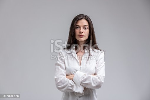 istock Long-haired woman standing with arms crossed 967091776
