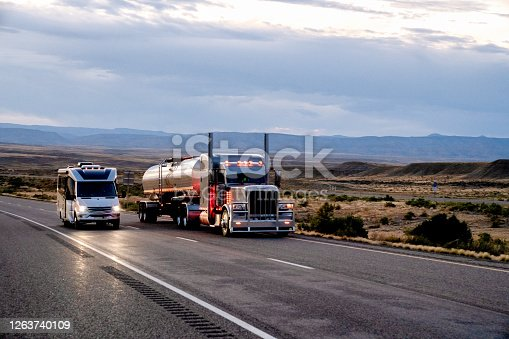 Long-Haul Semi-Trailer Tractor Truck Tanker being Passed by a Class C Motor Home on a Four-Lane Highway in the Desert Under a Dramatic and Cloudy Sky
