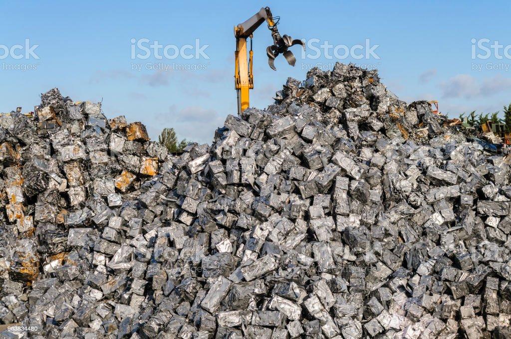 Ein Long-Reach-Ausgrabung-Grabber erreicht für Schrott Metall Würfel auf einem Schrottplatz – Foto