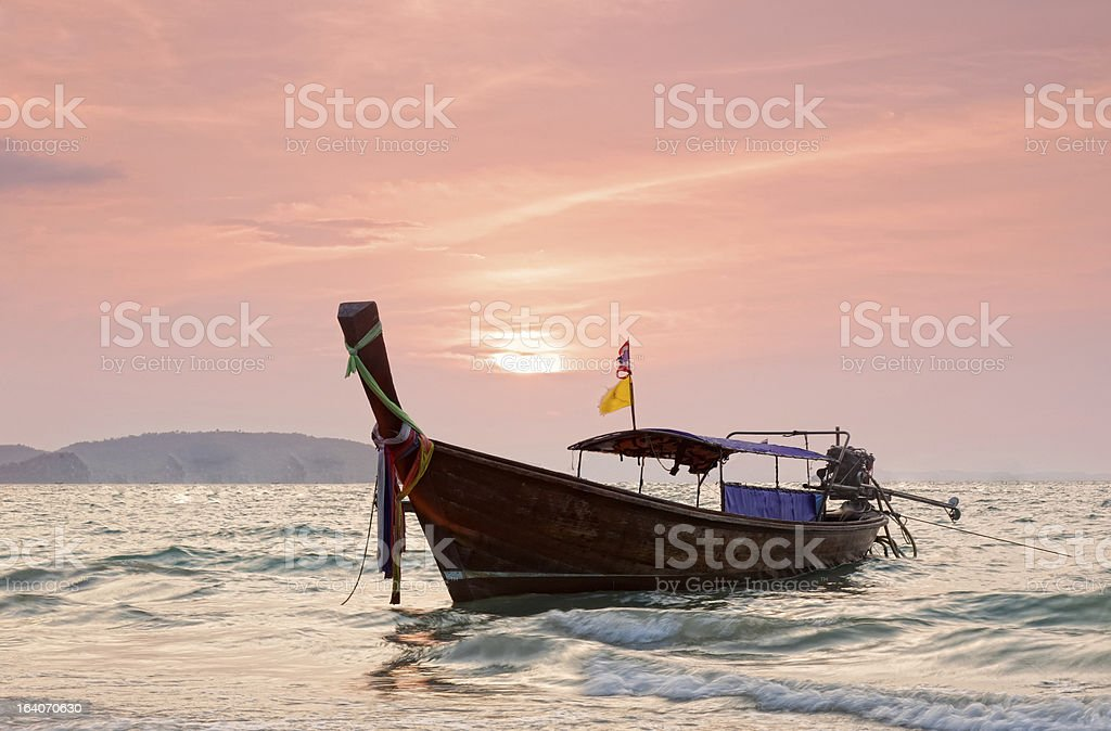Longtail boats against a sunset royalty-free stock photo