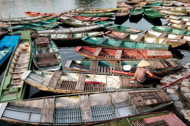 langschwanzboote, die traditionell von nordvietnamesen auf der anlegestelle verankert sind - holu stock-fotos und bilder