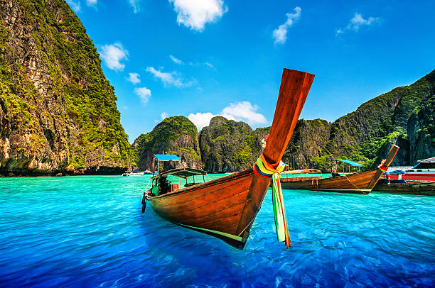 a longtail wooden boat at maya bay, thailand - phuket stock photos and pictures